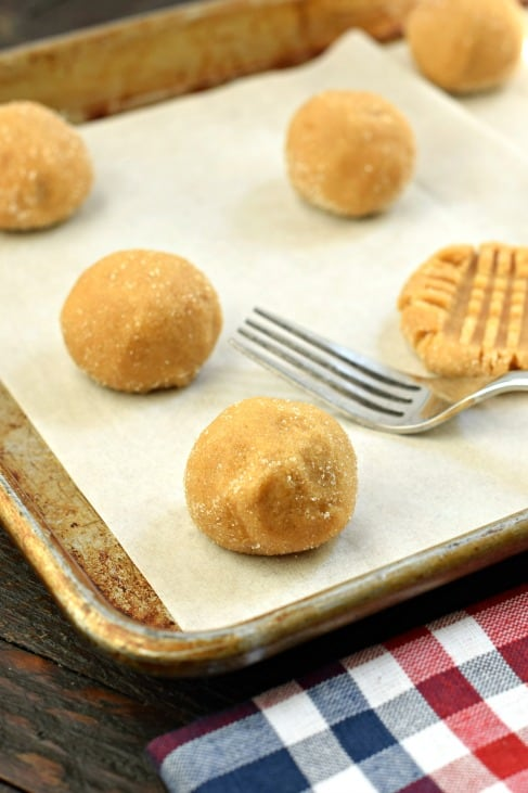 Peanut butter cookie dough rolled in granulated sugar and placed on a parchment paper lined baking sheet.