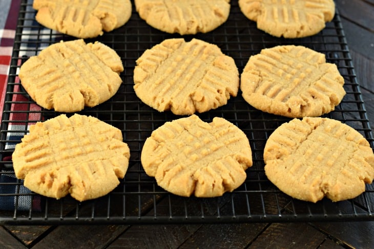 Baked peanut butter cookies on a black wire rack.