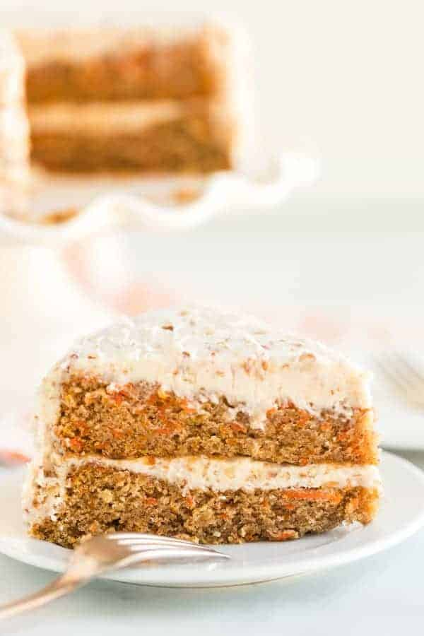 Carrot Cake slice with cream cheese frosting and chopped pecans on white plate