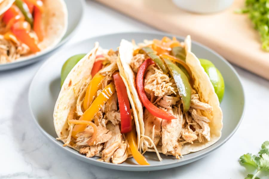 Chicken and sliced peppers on a flour tortilla on a gray plate.