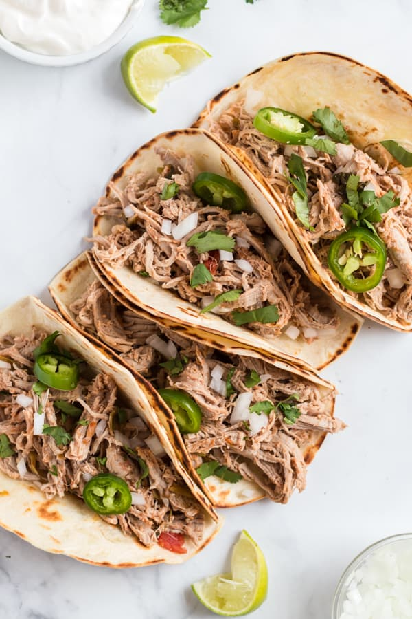 Pork Carnitas on cooked tortillas with onion, cilantro, jalapeno, and lime.