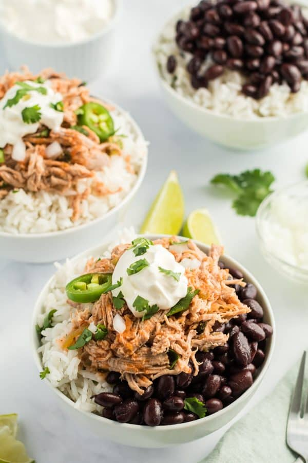 Shredded Pork Carnitas in bowl with cilantro lime rice, black beans, sour cream, jalapeno, and cilantro.