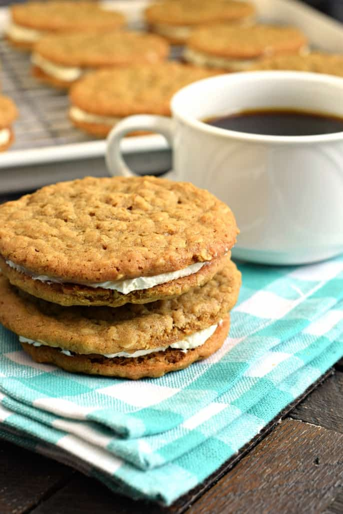 Teal and white checkered napkin topped with two oatmeal cream pies and white mug of coffee.