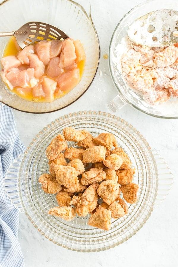 Prep bowls with chicken in egg mixture, chicken in flour mixture, and crispy chicken