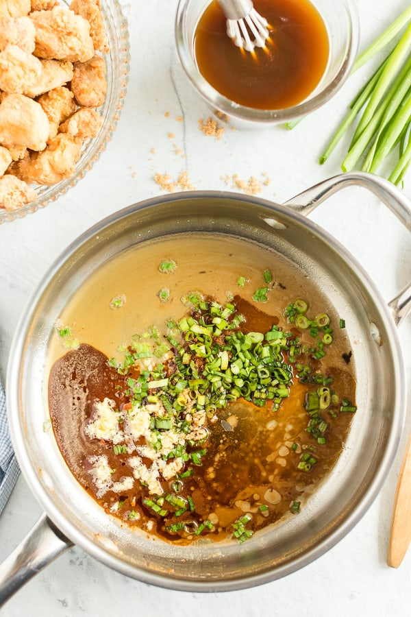Pot with orange chicken sauce and seasonings before being mixed.