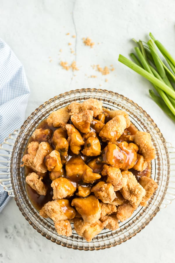 Glazed chicken with orange sauce in a clear glass bowl.