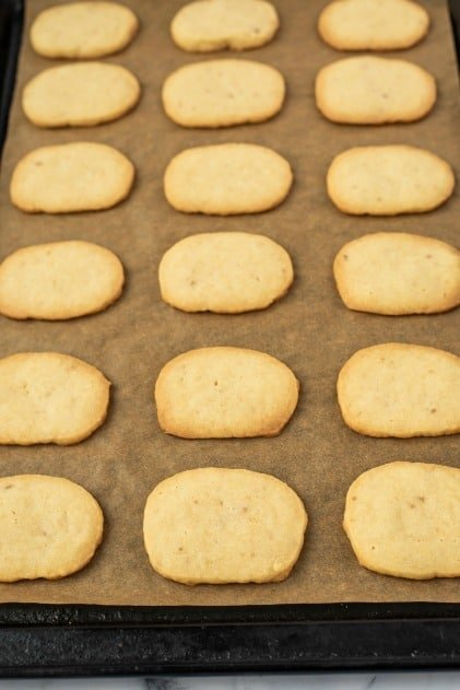 Parchment paper lined baking sheet with cooked cookies.