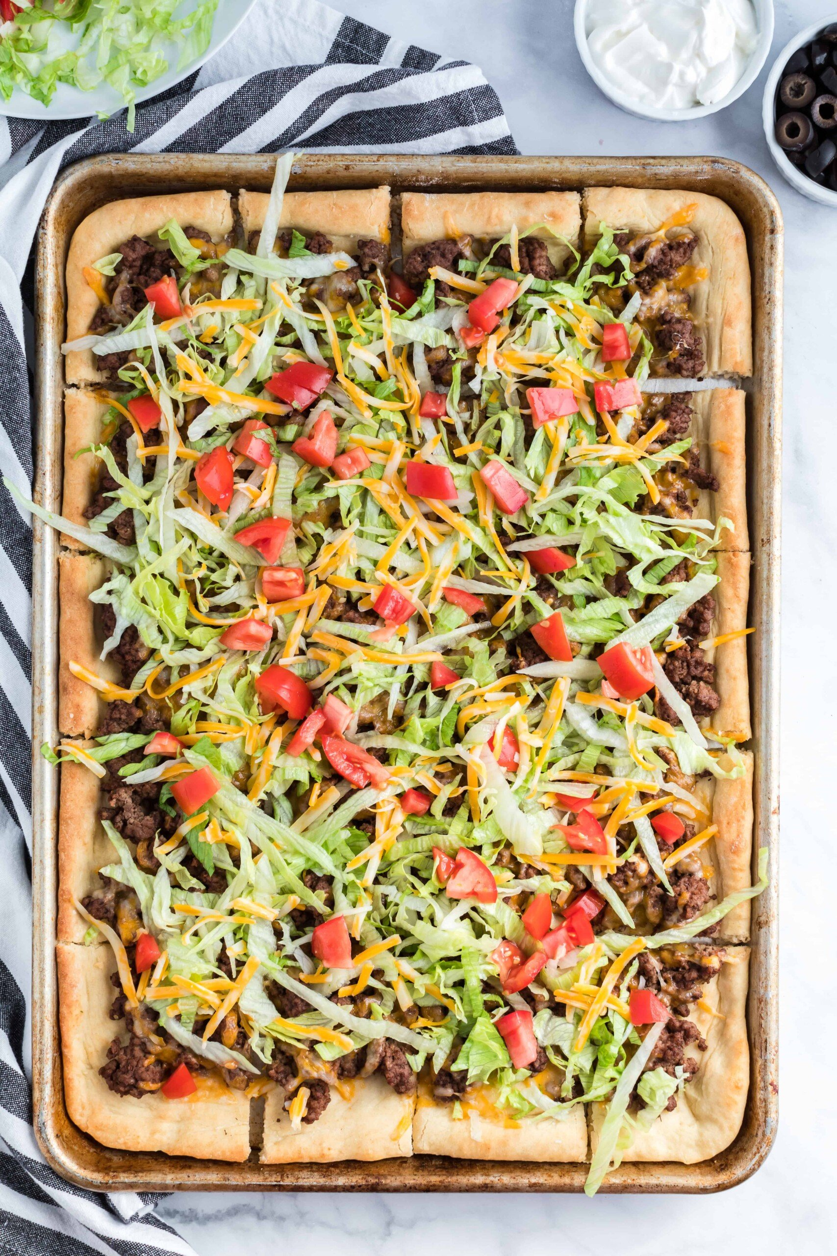 Baked taco pizza in a metal pan topped with lettuce and tomatoes.