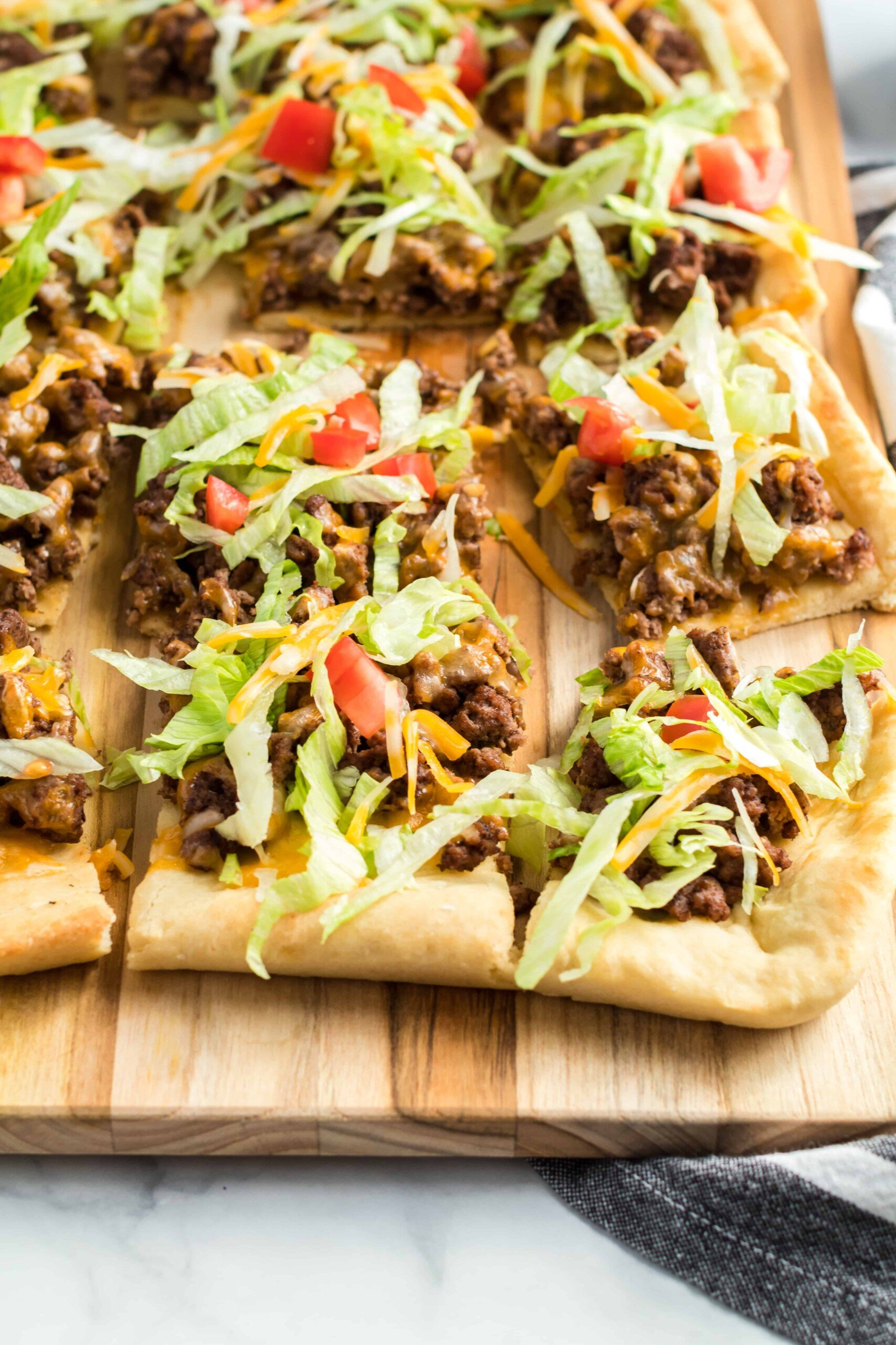 Beef taco pizza with lettuce and tomato cut on a wooden cutting board.