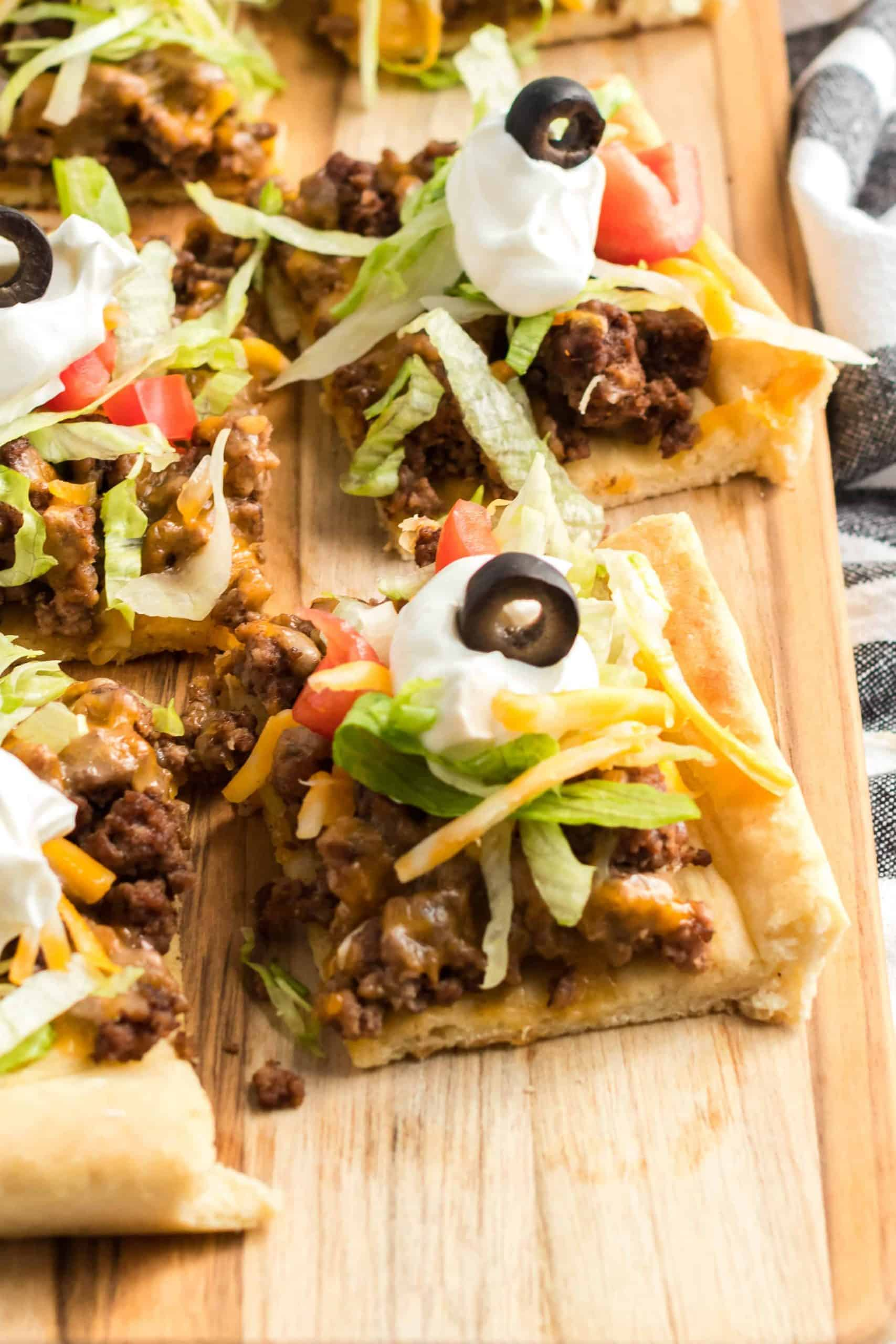 Taco pizza cut into small squares on a wooden cutting board.