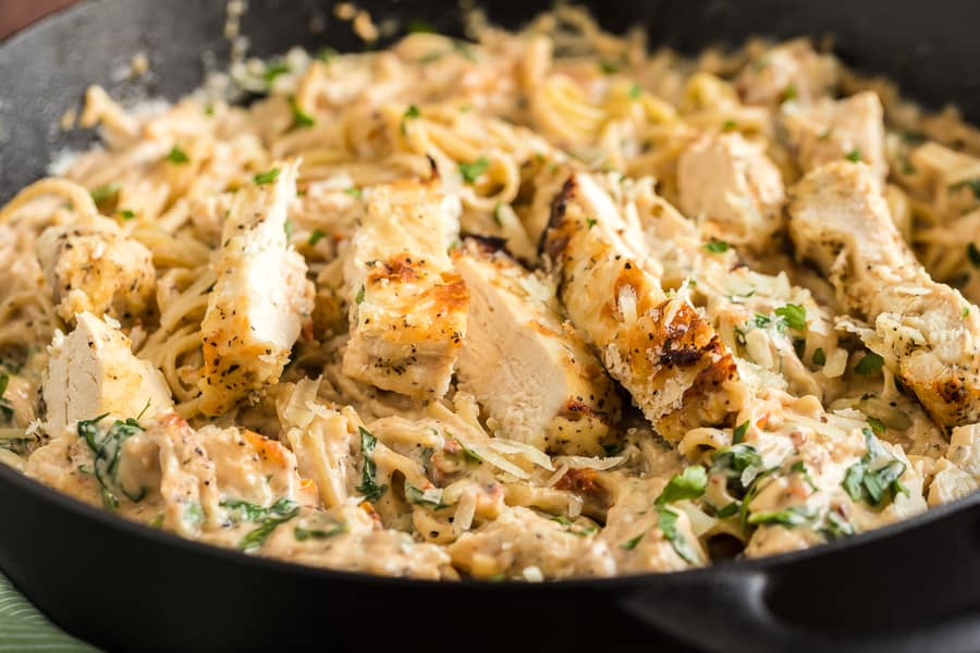 Large black skillet with creamy italian chicken pasta.