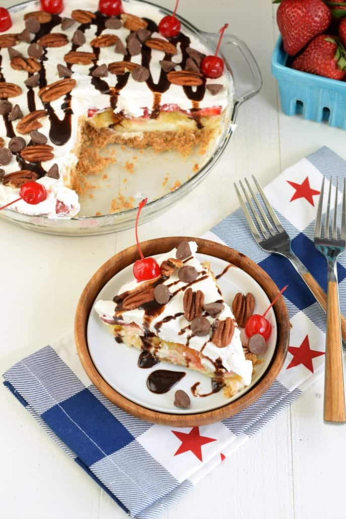 Slice of cheesecake topped with whipped cream, chocolate, pecans, and cherry on a white plate with red, white, and blue napkin.