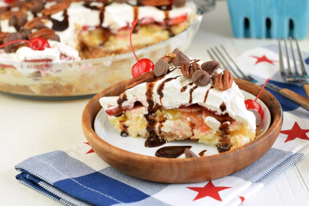 Banana Split cheesecake on a serving plate with fork.