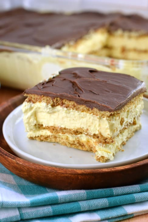 One square slice of chocolate eclair cake with layers of graham cracker, pudding, and chocolate frosting, on a white plate and teal napkin.