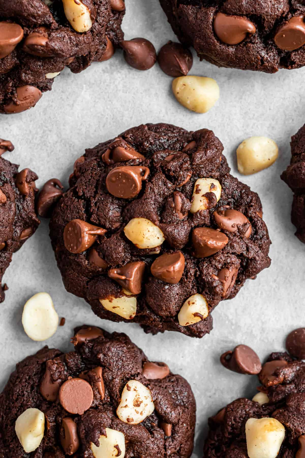 Chocolate macadamia nut cookies on a parchment paper lined cookie sheet.