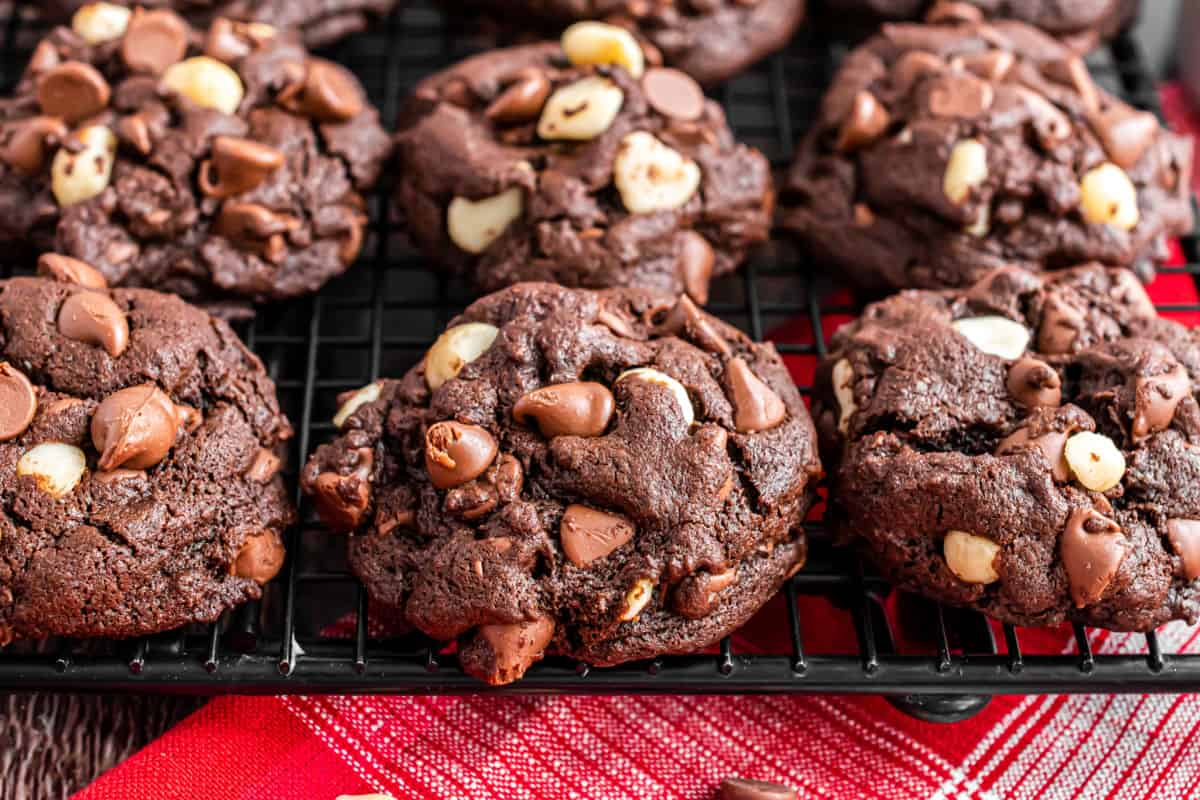 Chocolate cookies with macadamia nuts stacked on a wire cooling rack.