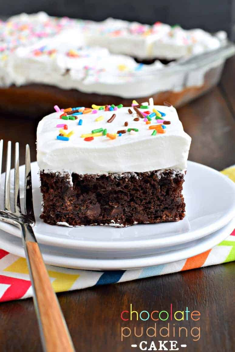 Dense chocolate cake with whipped cream and sprinkles on a white dessert plate.
