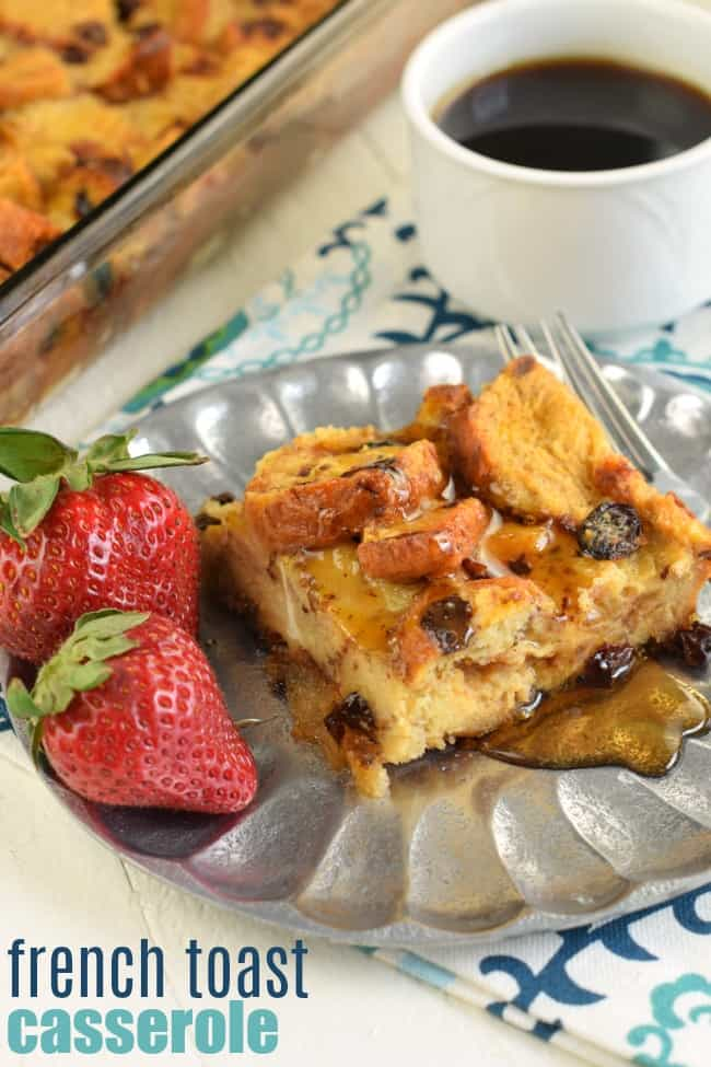 Slice of french toast casserole with two strawberries and maple syrup.