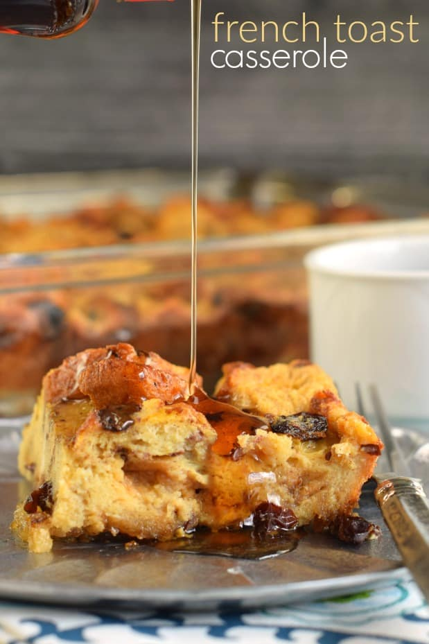 Slice of french toast casserole with raisins on a silver plate with maple syrup being poured over the top.