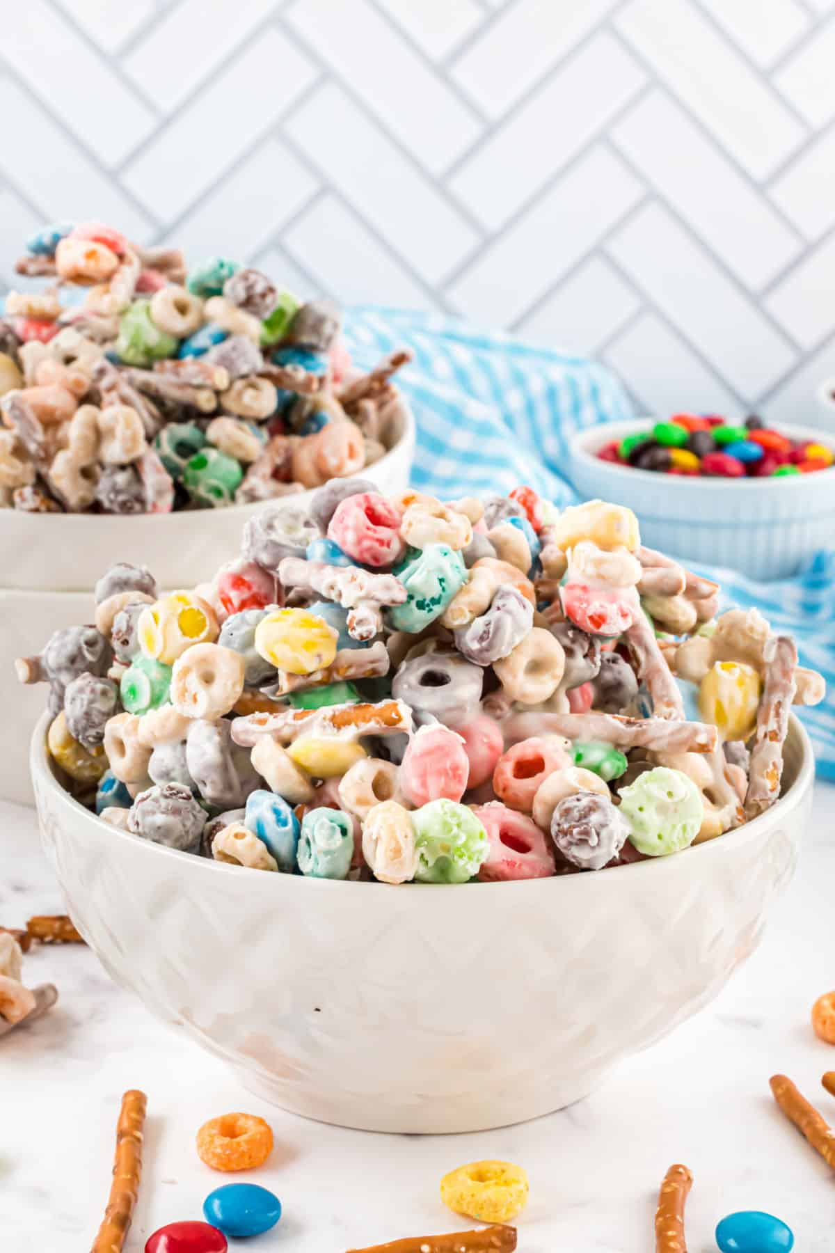 Easy candy mix made with cereal, white chocolate, and m&ms in a white bowl.