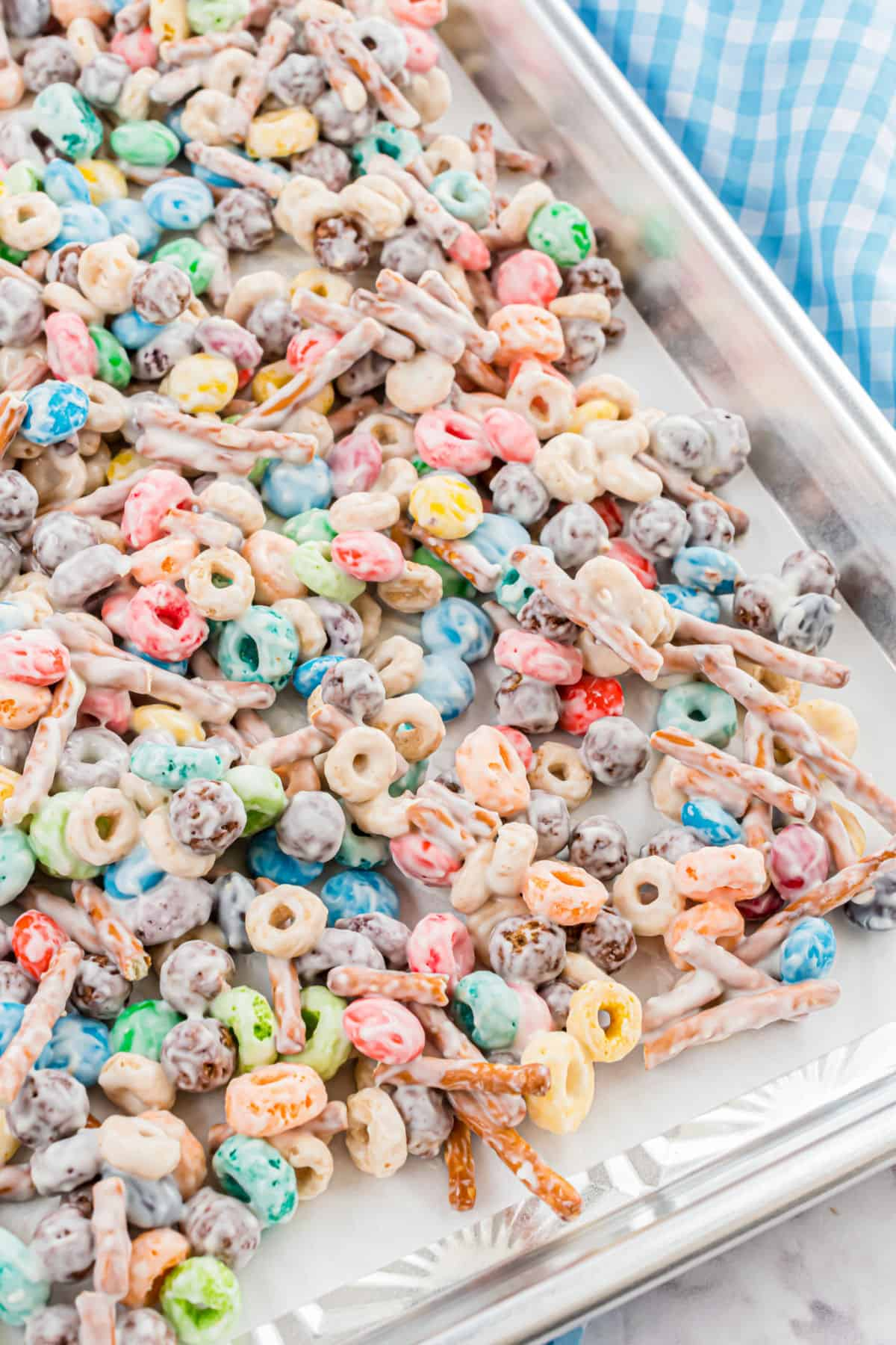 White trash candy mix spread onto a parchment paper lined cookie sheet.