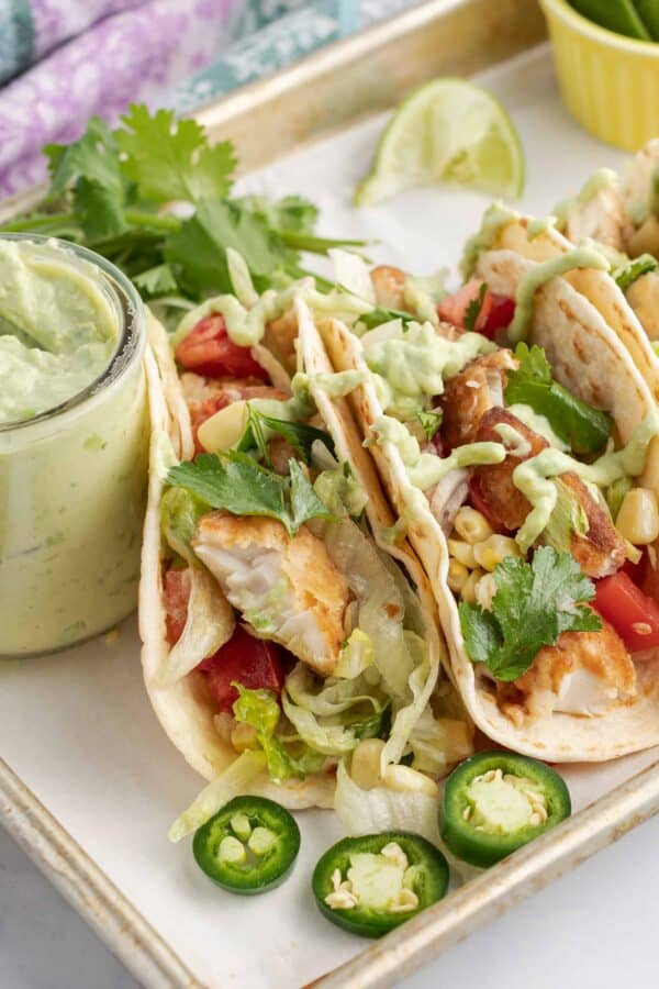 Fish Tacos on flour tortillas with lettuce, tomato, jalapeno, avocado sauce, and lime