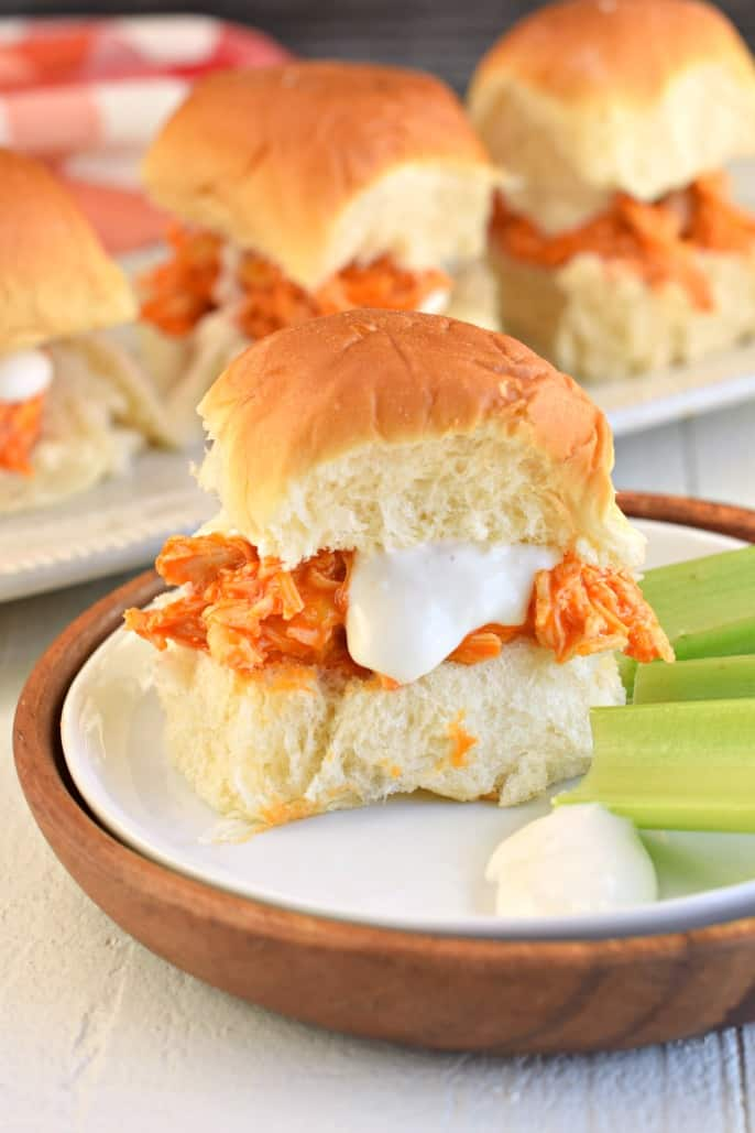 White plate with a hawaiian roll filled with shredded buffalo chicken a blue cheese sauce, with a side of celery sticks.