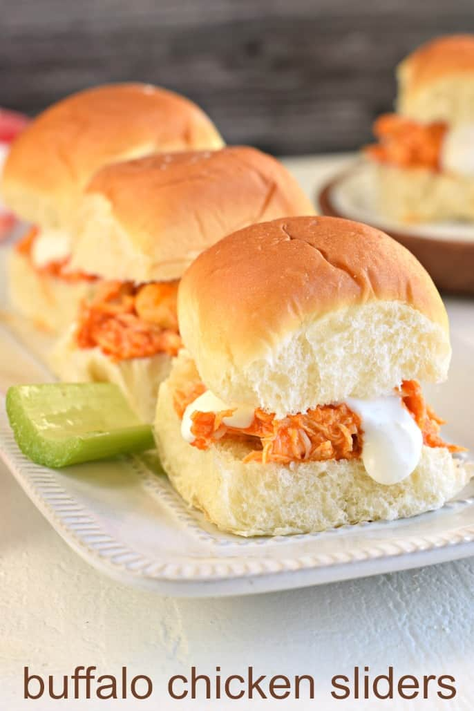 White serving plate with bleu cheese and buffalo chicken sliders.
