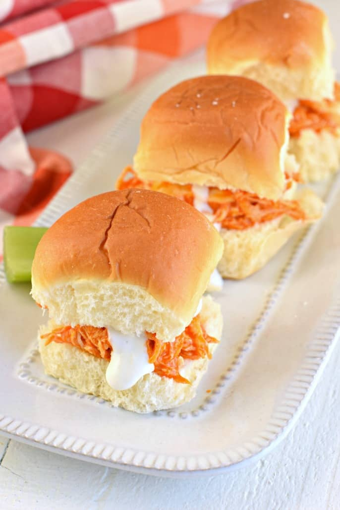 Shredded chicken with buffalo wing sauce and blue cheese dressing on a dinner roll.
