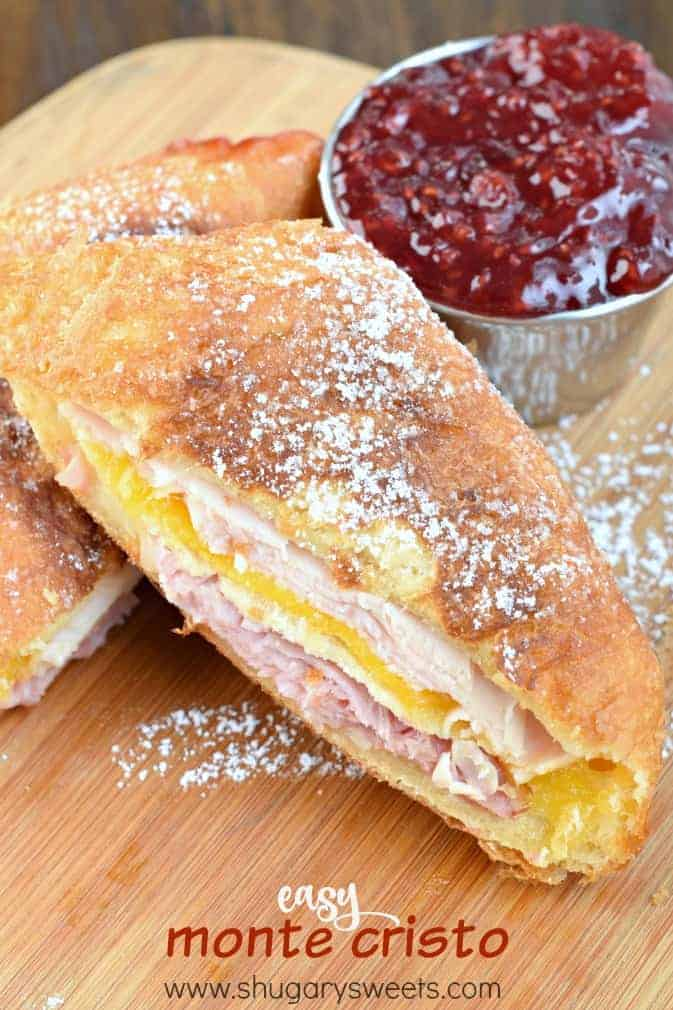 Wooden cutting board with half a slice of monte cristo sandwich (turkey, cheese, ham). Deep fried and sprinkled with powdered sugar and a side of raspberry jam.