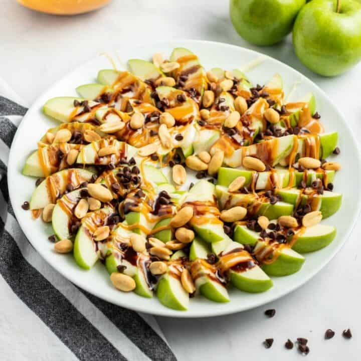Green apple slices arranged on a white plate in a spiral and topped with melted marshmallow, chocolate, caramel, and peanuts.