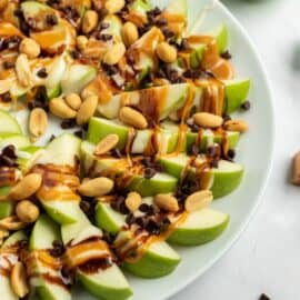 Apple nachos on a plate with green apple slices, caramel, chocolate, and melted marshmallow.