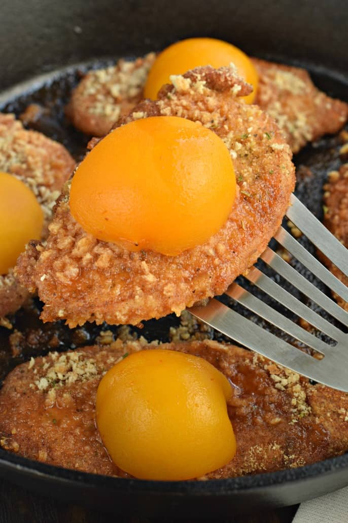 Cast iron skillet with a metal spatula lifting a shake and bake cooked pork chop with peaches.