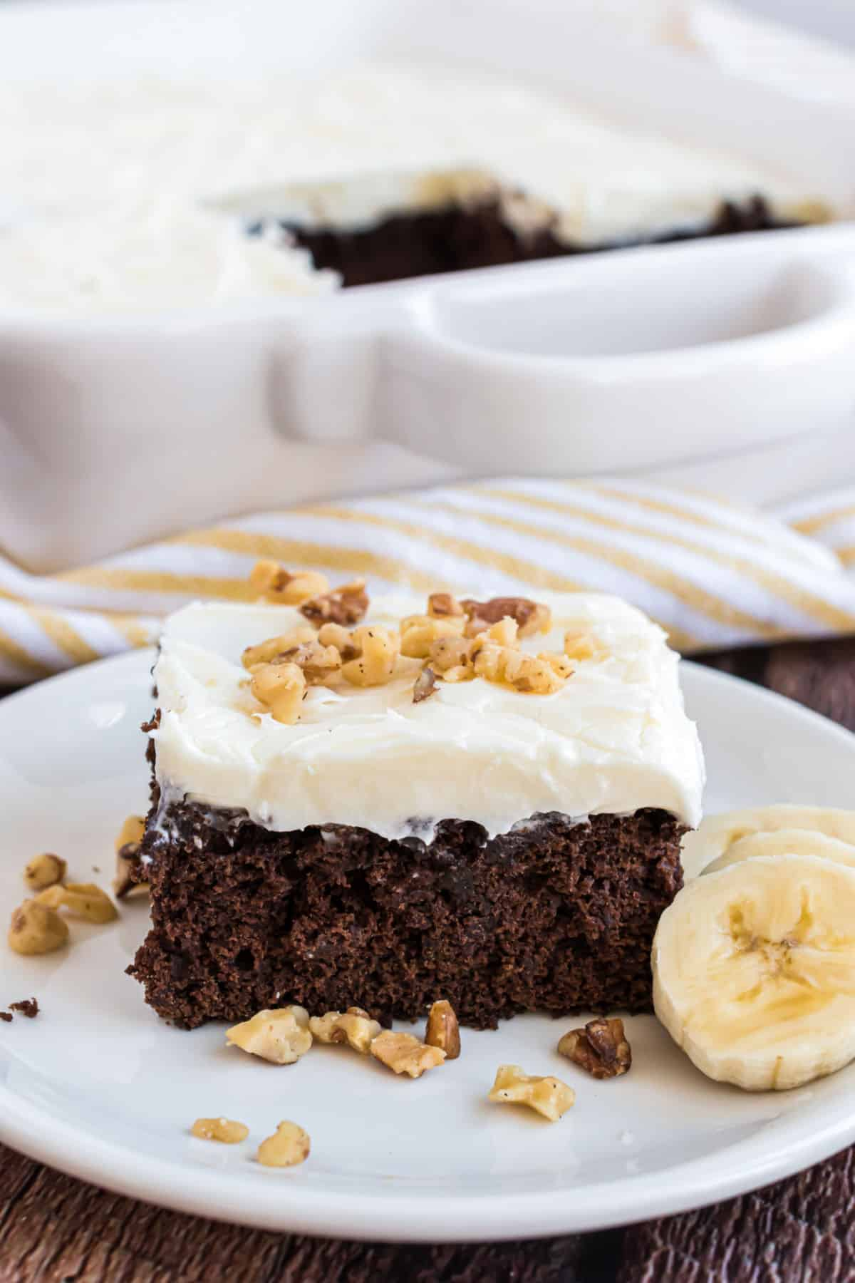 Chocolate banana cake with cream cheese frosting and walnuts served on a white plate.