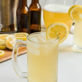 Beer mug with homemade summer shandy, garnished with a lemon slice.