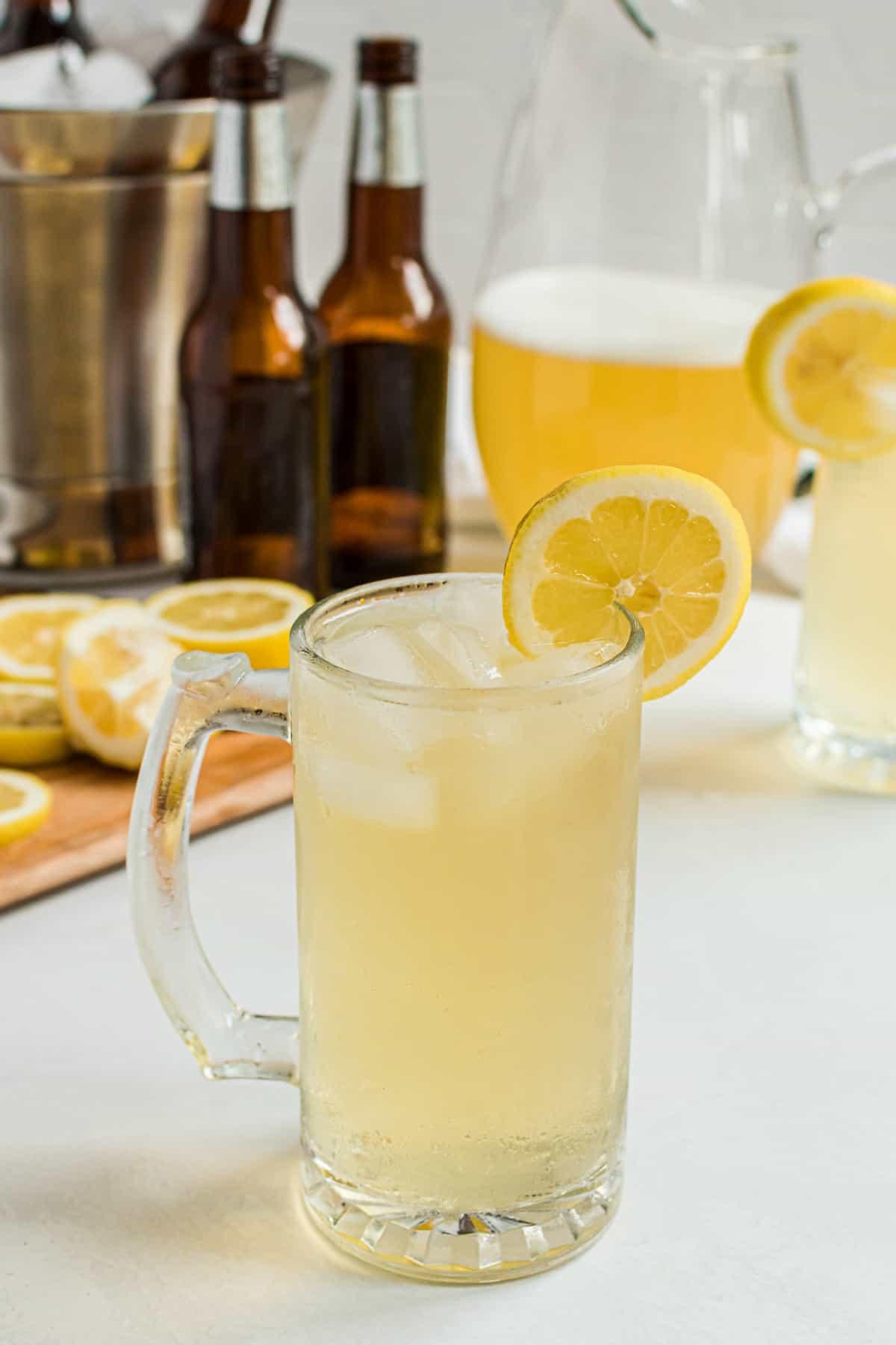 Beer mug with homemade summer shandy, garnished with a lemon slice.