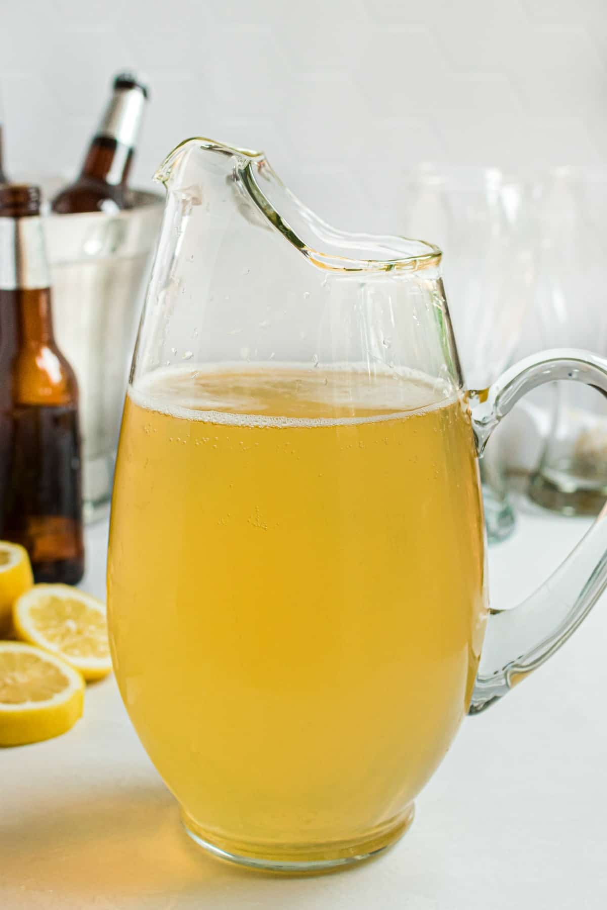 Clear glass pitcher of homemade lemon shandy with bottles of beer in background.
