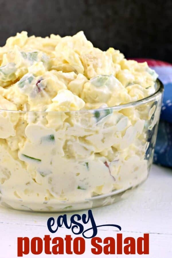 Clear glass bowl filled over the top with homemade potato salad.
