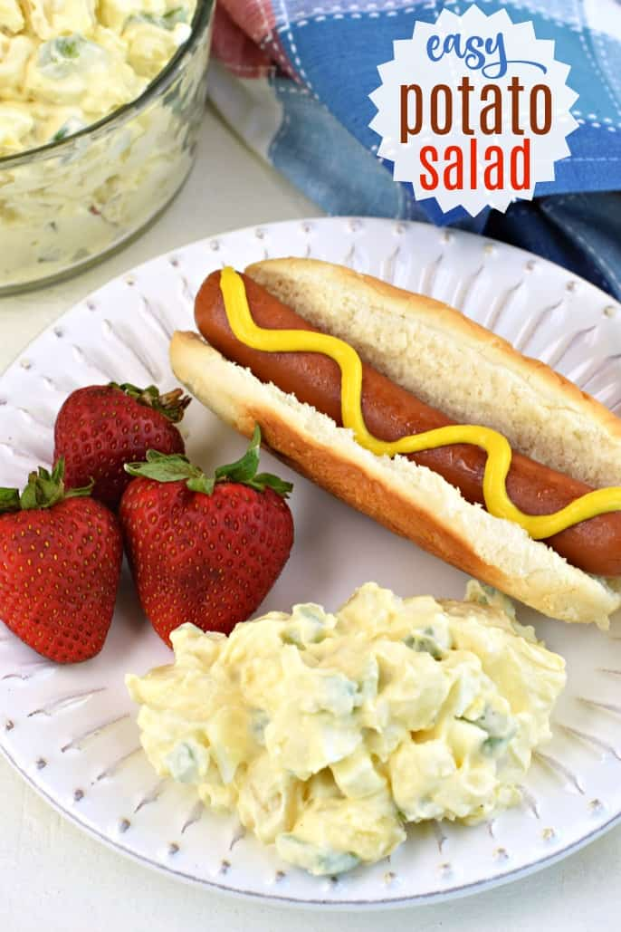 White dinner plate with a dollop of potato salad, three red strawberries, and a hot dog on a bun with mustard.