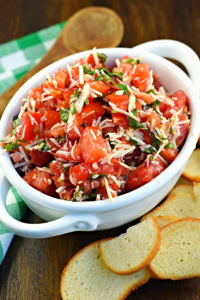White bowl with fresh tomato bruschetta and a wooden spoon to serve.