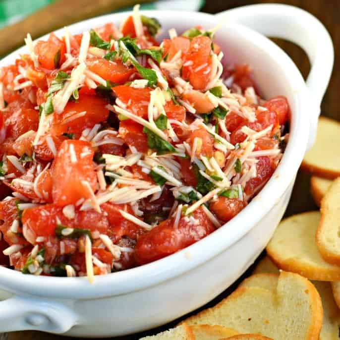 Fresh tomatoes and garden-grown basil come together to create the most delicious and EASY Bruschetta recipe. Use bagel chips or toasted bread to dip, or add this mixture to pasta with cheese!
