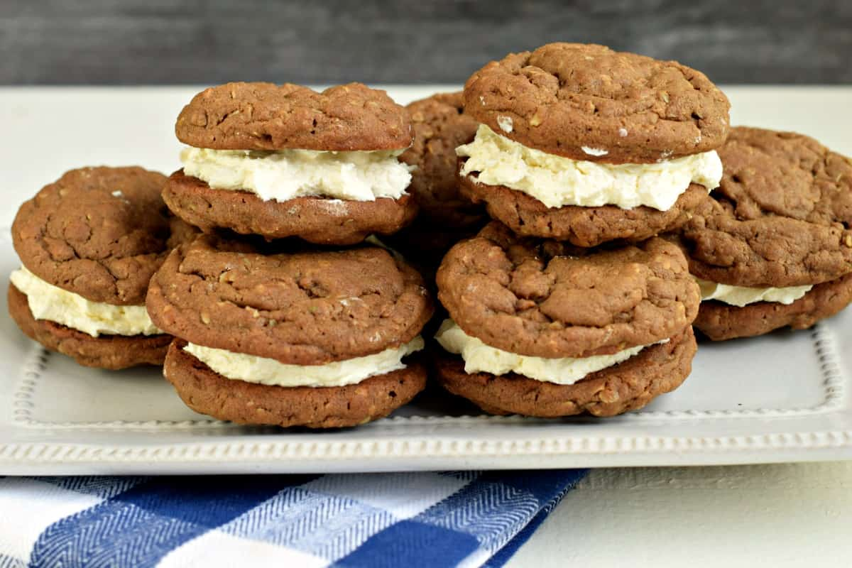 Stack of chocolate oatmeal cream pies on a white platter.