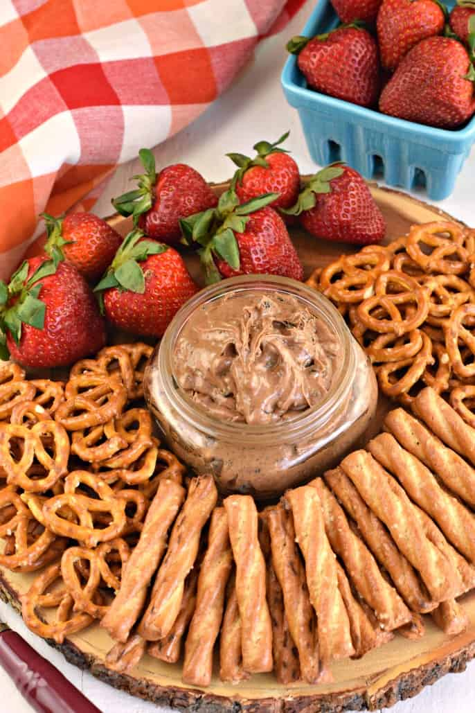 Small clear glass mason jar with oreo peanut butter dip on a wooden serving plate with strawberries and pretzels.