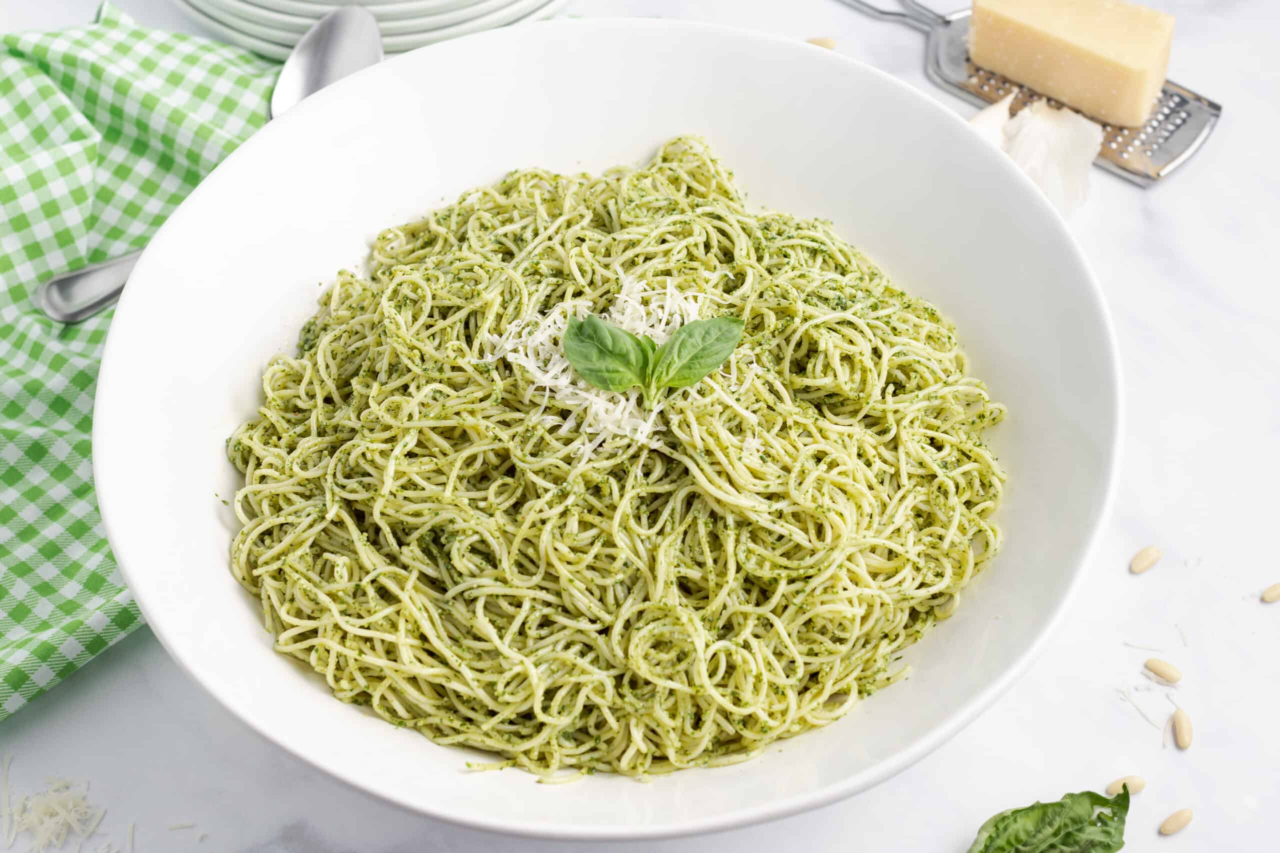 Pesto pasta with parmesan cheese in a white serving bowl and cheese grater on the side.