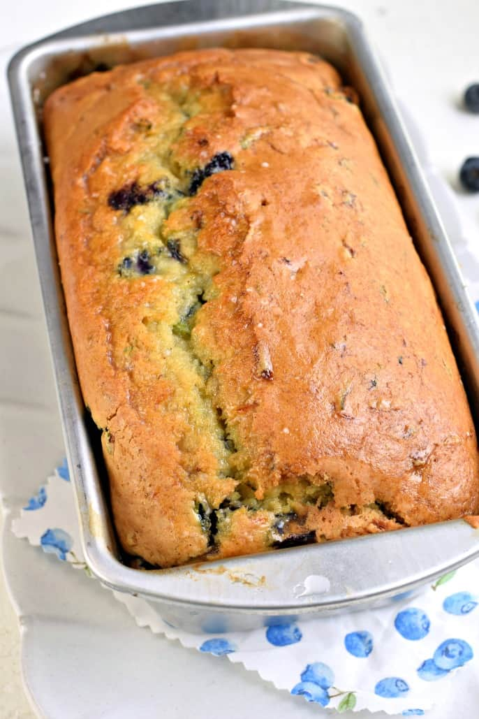 Baked loaf of zucchini blueberry bread in metal loaf pan.