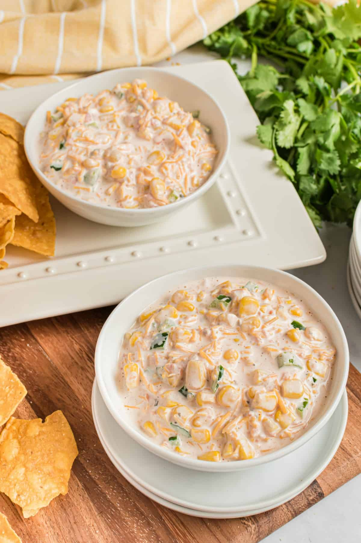 Two white bowls filled with creamy jalapeno corn dip with a side of tortilla chips.
