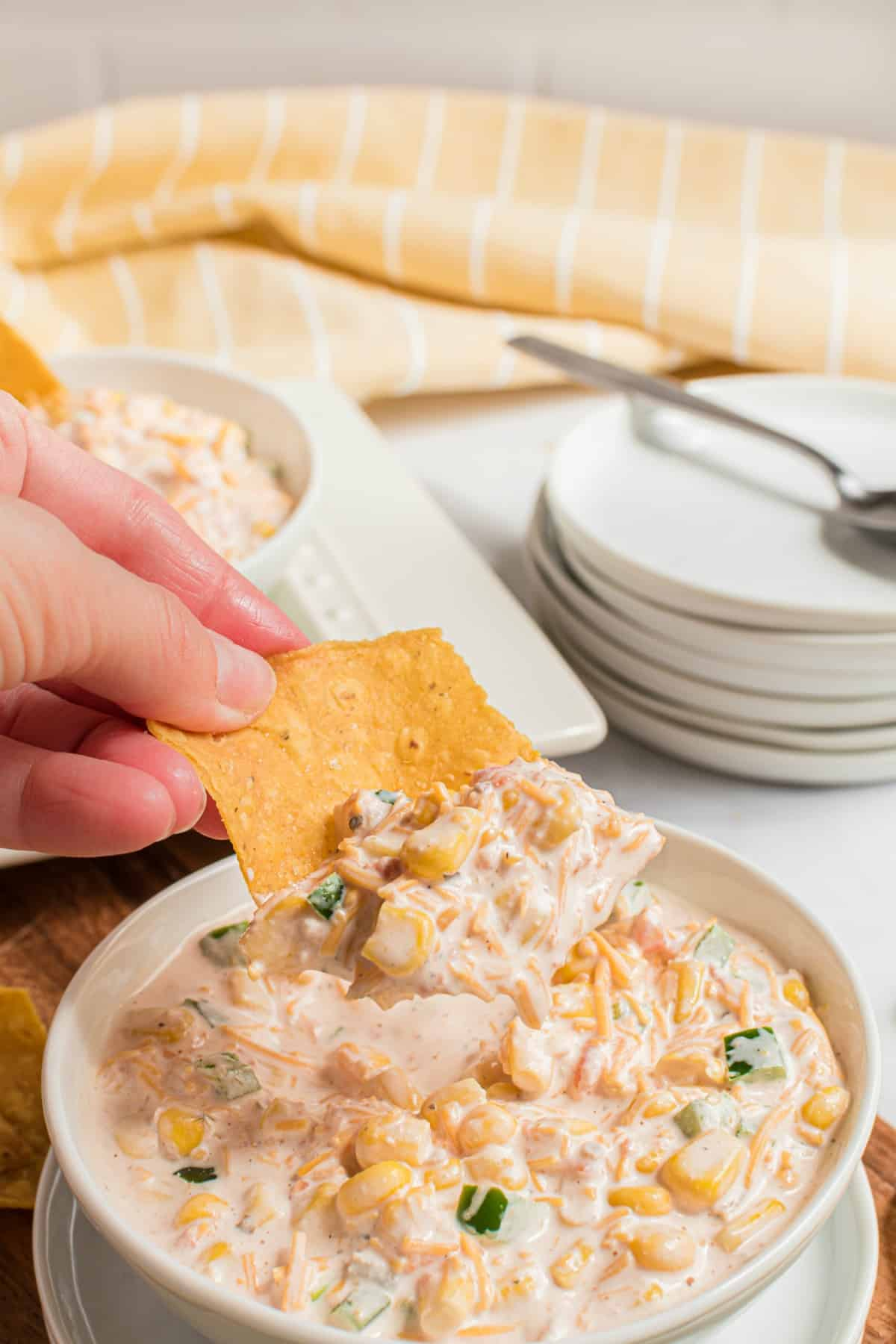White bowl with corn dip and a tortilla chip being scooped in the dip.