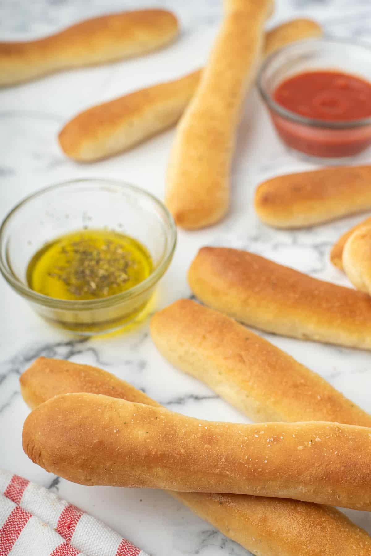 Marble counter with breadsticks laying on top with small bowls of marinara and oil.