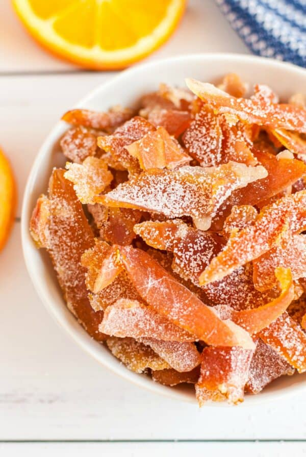 Slices of orange peel coated in sugar in a white bowl.