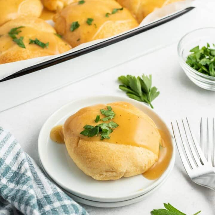Chicken kisses in a 13x9 baking dish with one removed and placed on a white dinner plate. Topped with gravy and parsley.
